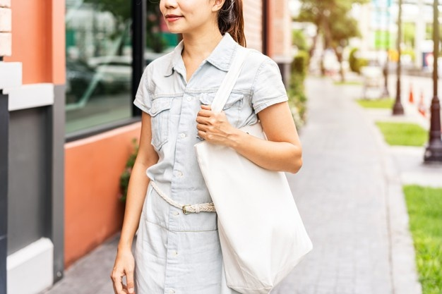 Young lady carrying a tote bag that is environmentally conscious and eco-friendly promotional items